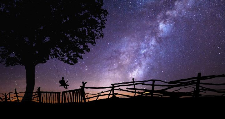 child on a swing looking at starry night